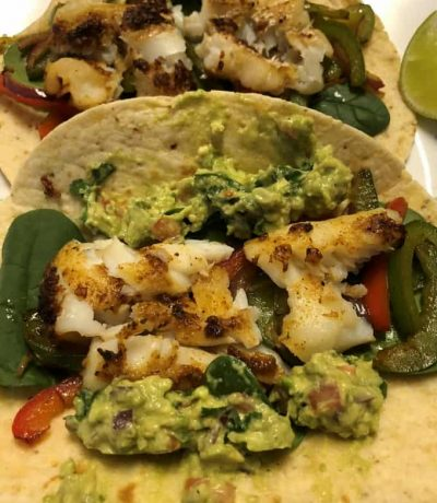 Fish taco is a good dish for dinner or lunch. Crisped the fish in the Air Fryer, it can be baked in oven or in a pan. Season the veggies in a pan. Just assemble the lightly crisped corn-flour tortilla by layering spinach, veggies and fish. Spread the guacamole on the taco and enjoy!