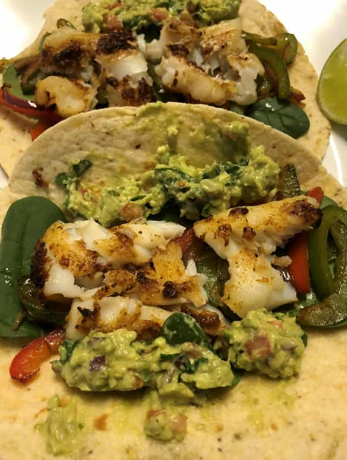 Fish Tacos is a good dish for dinner or lunch. Crisped the fish in the Air Fryer, it can be baked in oven or in a pan. Season the veggies in a pan. Just assemble the lightly crisped corn-flour tortilla by layering spinach, veggies and fish. Spread the guacamole on the taco and enjoy!